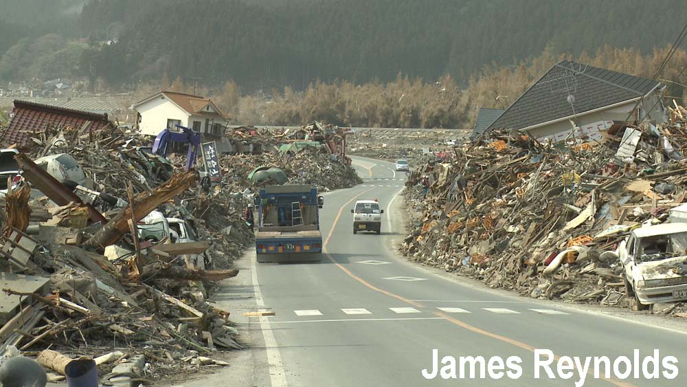 Road lined with tsunami debris through Rikuzentakata