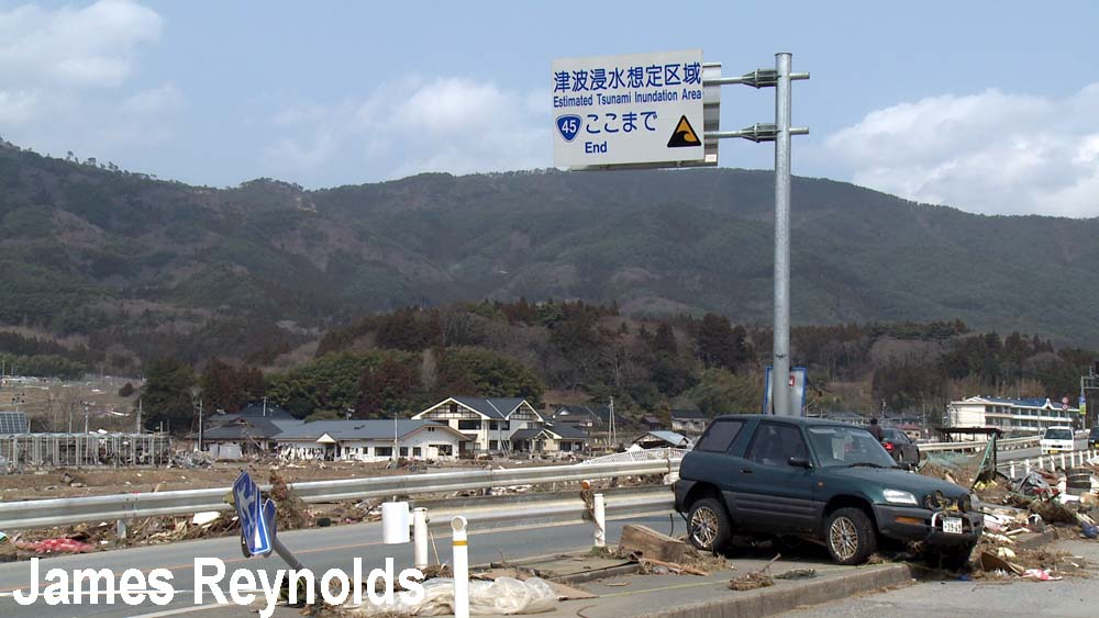 Car washed up against tsunami warning sign in Rikuzentakata